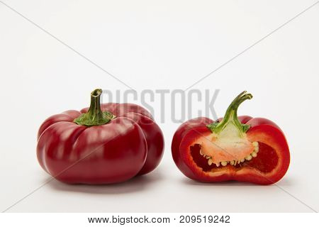 Two ripe red peppers in a cut with seeds on a white background