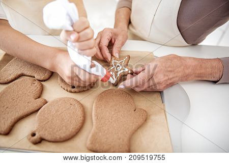 Close up top view of granny hands holding sweet pastry in shape of star. Girl is squeezing cream on it from tube accurately