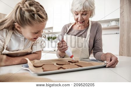 Friendly family is decorating self-made sweet pastry. They are standing in kitchen and smiling