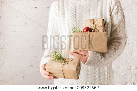 Female hands holding many boxes with presents for Christmas. New year's concept. Settle background kinfolk . Copy space