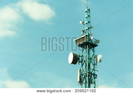 Telecommunication antennas outdoor on the tall metal pole construction with digital clock display and blue sky background close up