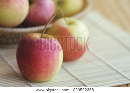 Stack of fuji apple in basket and on wood table for background or wallpaper. Delicious sweet and juicy fuji apple suitable for salad cooking or bakery. Fuji apple has origins in Japan. Fresh fuji apple for background with copy space.