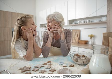 Pretty housewives. Excited girl is looking at her granny with joy and laughing. They are standing at table with dough and flour on it