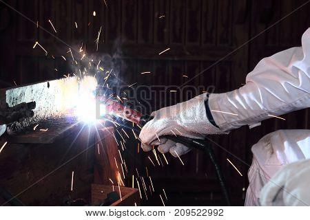 Hands of professional industrial welder with torch and protective gloves welding metal steel with spark in the factory.