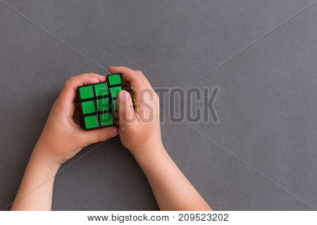 Moscow Russia August 24 2017: Rubik's cube in child's hands closeup grey background. Boy holding Rubik's cube and playing with it.