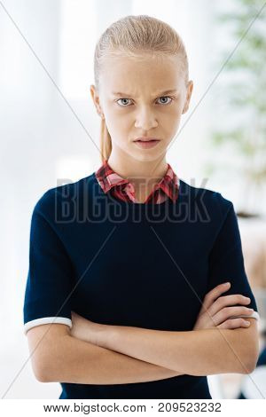 Angry look. Cheerless nice blonde girl standing cross handed and looking at you while being angry