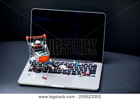 Laptop And Pills In Small Shopping Trolley