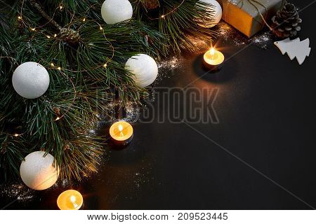 Christmas. Xmas toys, burning candles and spruce branch on black background top view. Copy space. Still life. Flat lay. New year