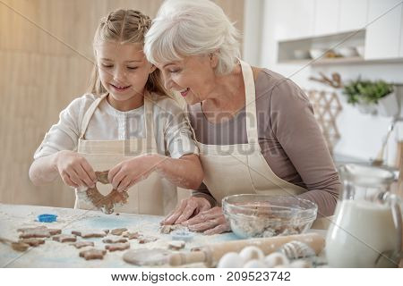 Portrait of happy girl showing self-made shape of dough to her grandmother. Senior woman is looking at it with joy and smiling while standing in the kitchen