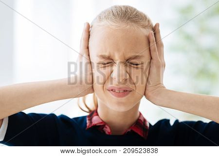 Stressed out. Angry nice blonde girl covering her ears and closing her eyes while being stressed out