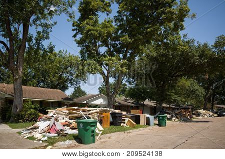 Houston Texas USA September 10 2017: Damaged houses on one of the streets. After hurricane Harvey. Trash and damaged households outside the houses.