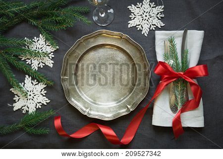 Christmas table setting with vintage dishware, silverware and snowflake decorations on gray linen tablecloth. Top view.