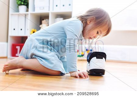 Toddler girl using a virtual reality headset in her house