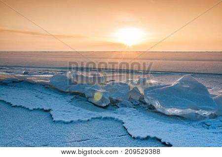Field of ice hummocks on the frozen Lake Baikal. Sunset. Russia