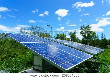 Solar Cell Generating Electricity And Installed In The Forest With Blue Sky And Cloud And Green Tree