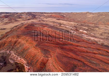 dusk over foothills of Rocky Mountains in northern Colorado with red sandstone and canyons, aerial view