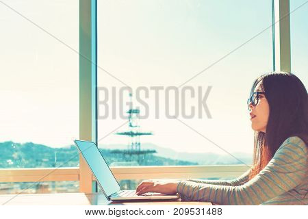 Woman working on her laptop in bright window lit room