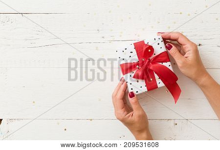 Top view on woman's hands holding nicely wrapped Christmas or birthday gift box with red satin ribbon on white wooden background.