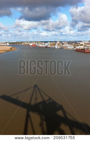 Port with cranes on the Daugava River in Riga, the capital of Latvia, with a shadow on the water with waves of a crane for the loading of Containers