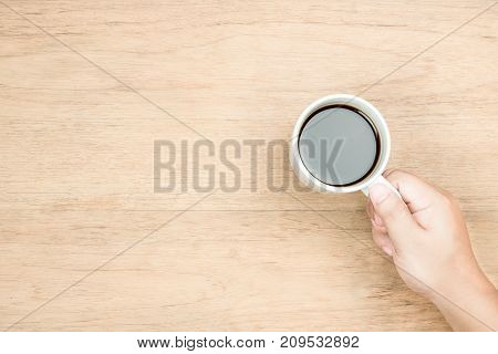 yellow brown hand hold white coffee cup on wood texture from top view right hand side empty area for copy space