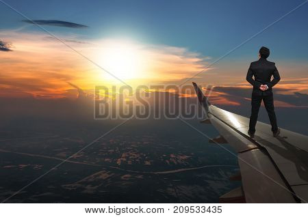 businessman standing looking the sunset on airplane wing Challenge business concept
