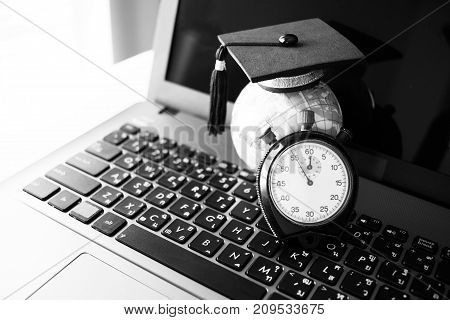 Time is Education Graduation cap on top model Earth near clock on computer. Concept of abroad international Educational times Studies lead to success in life Graduate study abroad program.