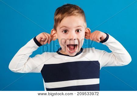 Funny happy young boy in sweater showing grimace at camera over blue background