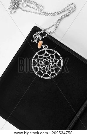 Dreamcatcher silver pendant with piece of amber in black jewel box closeup