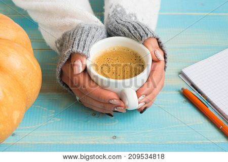 Woman's hands in sweater holding cup of coffee on the blue wooden table. Holiday concept. Girl holding a coffee cup on a wooden vintage background - winter time concept.Holiday concept.