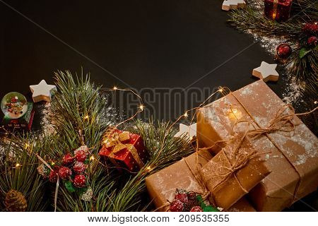 Christmas gifts and garland near green spruce branch on a black background. Christmas background. Top view. Copy space. Still life. Flat lay. New year