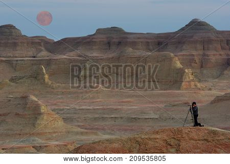Photographer take photo on the fantastic mountain background with full moon extremehuman scale adventure touring concept