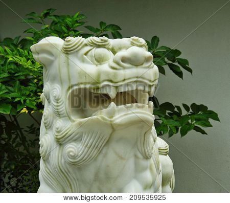 A white statue of a lion showing teeth and looking to the right.