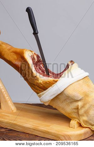 Whole jamon on a wooden stand and wooden table open from cloth and knife inside. Traditional Spanish food, Mediterranean food. Dried pork leg, salted pork hoof