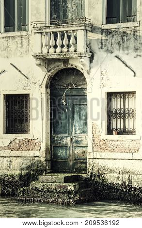 A vintage image of a door on a building along the Grand Canal of Venice.