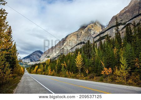The concept of active and automobile tourism. Powerful granite Rockies of Canada. The road 93
