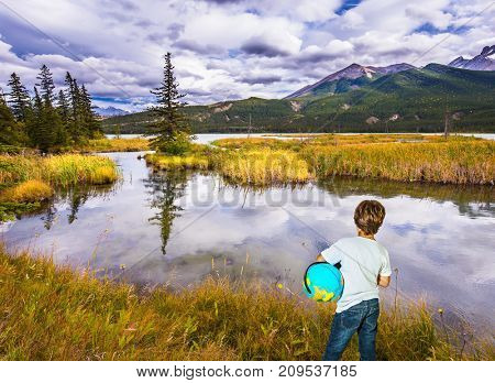 Trip to the Indian summer. Handsome boy with a globe in the Rocky Mountains. The concept of ecological and active tourism