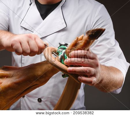 The cook in a white apron attaches the jamon to the wooden stand. Pig leg. Traditional Spanish ham.