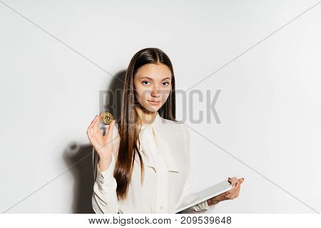 a young successful business lady holds a gold bitcoin in her hands and studies data on the crypto currency