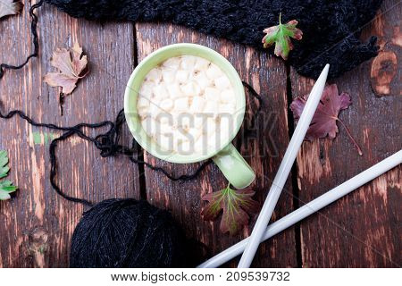 Cup Of Coffee Or Hot Chocolate With Marshmallow Near Knitted Blanket And Knitting Needles. Autumn Co