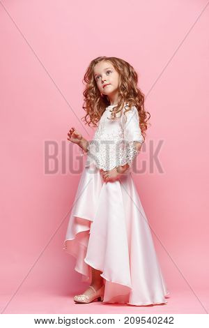 Full length of beautiful little girl in long dress standing and posing over pink background