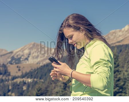 Sporty millenial texting her hiking achievements. Female hiker using mobile.