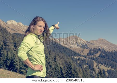 Female hiker pointing at mountain peak. Personal trainer motivating.