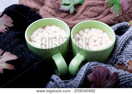 Two Cup Of Coffee Or Hot Chocolate With Marshmallow Near Three Knitted Grey, Black And Brown Sweater