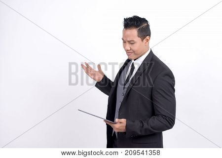 Asian businessman looking shocked while using his digital tablet receiving bad news technology news messages expressive lifestyle profession nervous concept
