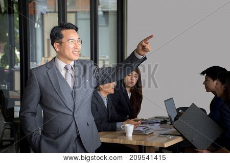 Portrait of businessman standing in front of her team at office,Asian Businessman leading her team over a white background, team work concept