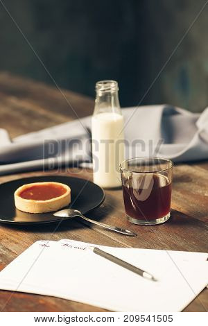 The pencil, paper, coffee, cake and milk on office table