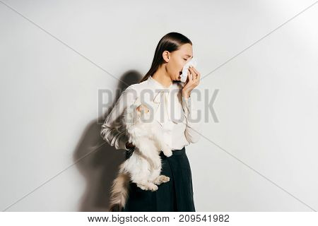 the girl sneezes into the handkerchief because she is allergic to the cat she is holding in her hands
