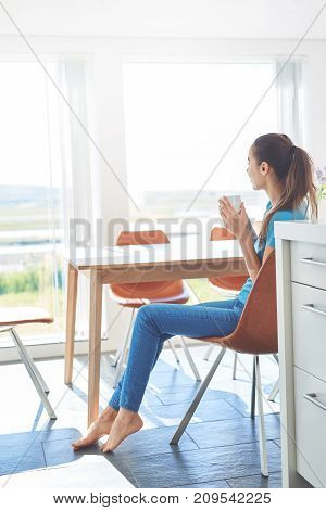 a young woman sits with a cup of coffee on the kitchen at morning. Woman holding a cup of coffee in her kitchen