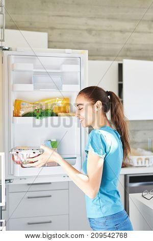young woman cooking breakfast in the kitchen. woman gets food out of the refrigerator