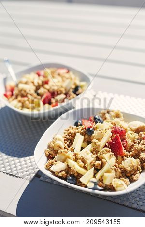 plates with fresh fruit salad, Granola and berries in the morning on the veranda. Delicious, quick and healthy light breakfast for energetic people